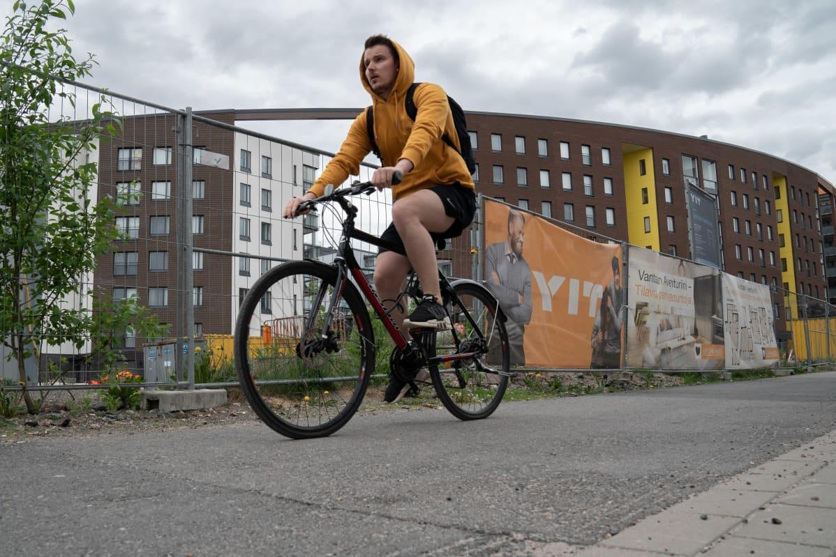 Palveluja saa vielä odottaa Vantaan Kivistössä. Naapurustokaan ei ole ihan vielä valmis. Alueelle kaavaillaan lisärakentamista jopa 30000 uudelle asukkaalle. Nyori mies pyöräilee työmaaaitojen edessä.