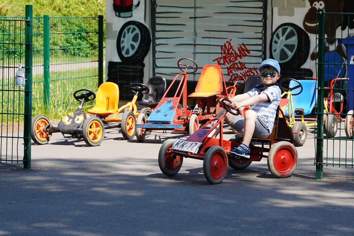 lapsi istuu punaisessa polkuautossa valmiina ajamaan