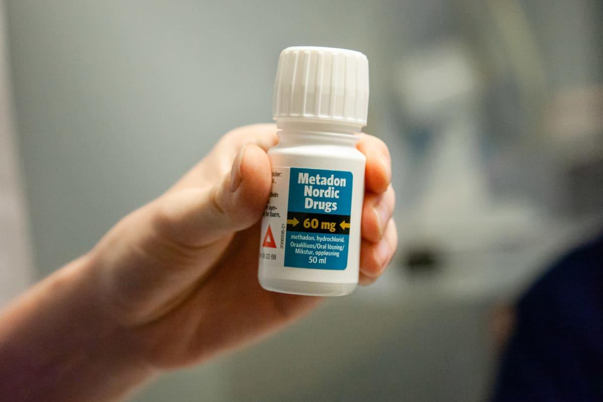 60 mg Metadon-purkki korvaushoidon asiakkaan kädessä.