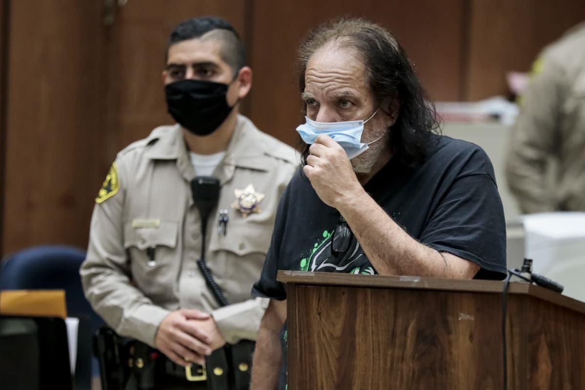 Aikuisviihdetähti Ron Jeremy kuulemassa syytettä kasvomaski päällään.
