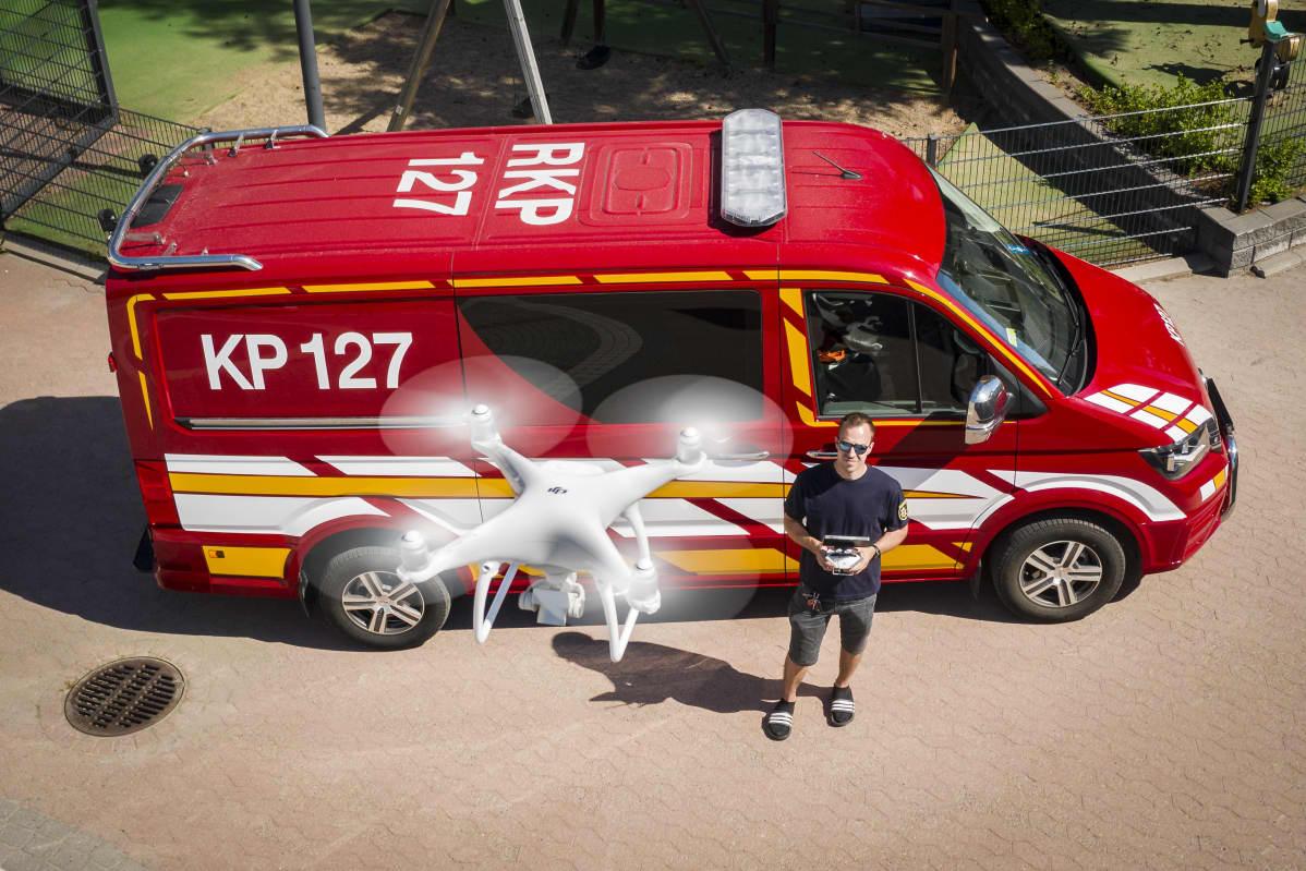 Etualalla drooni lennossa. Taka-alalla paloauto ja pilotti.