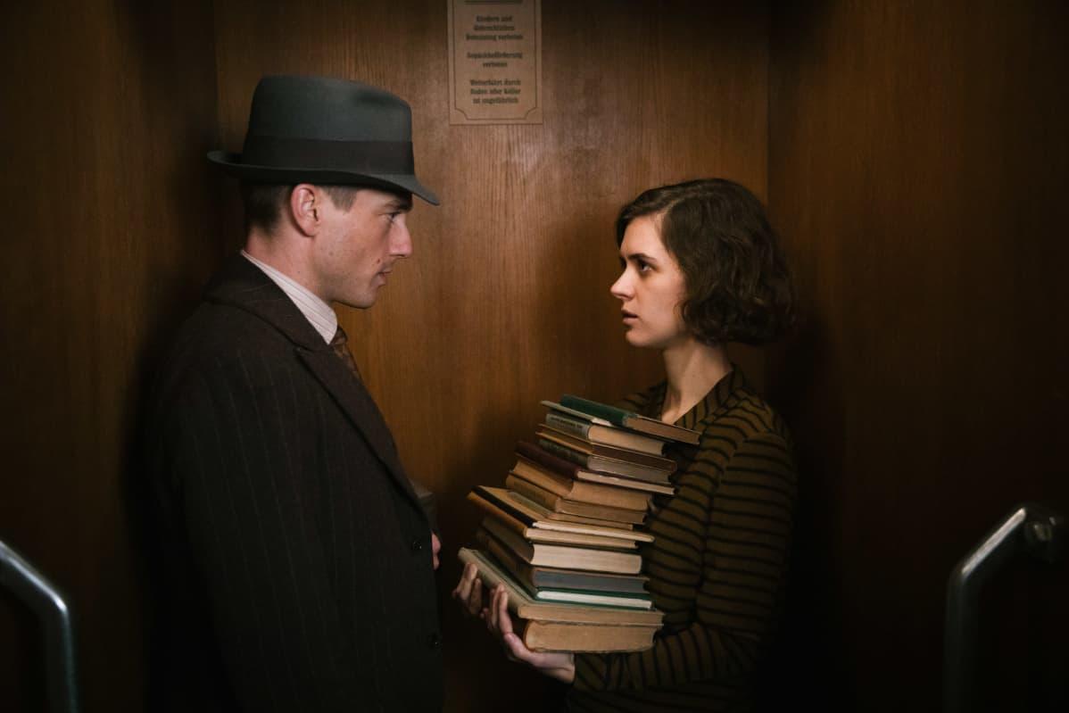 Gereon Rath (Volker Bruch) ja Charlotte Ritter (Liv Lisa Fries) seisovat vastakkain. Charlottella on pino kirjoja sylissään.