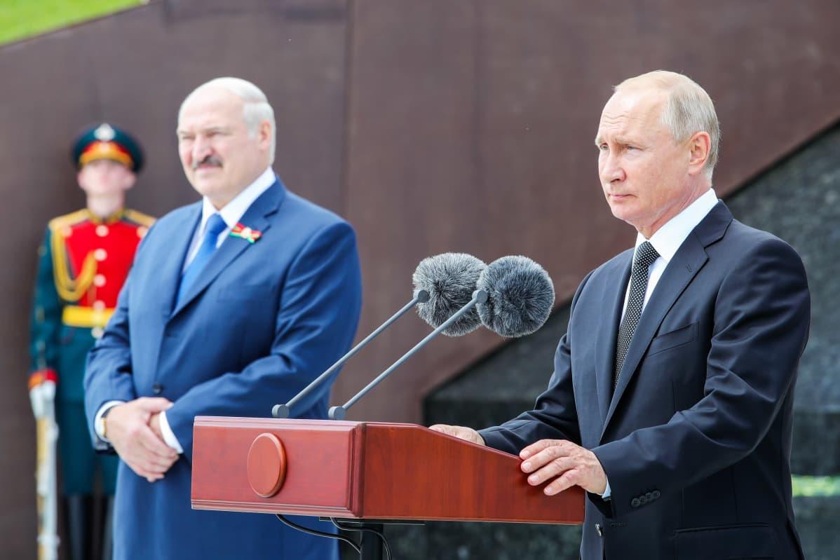 Aljksandr Lukašenka ja Vladimir Putin seisovat Rževissä muistomerkin edustalla. Putinilla on edessään puhujanpönttö ja kaksi mikrofonia. Taustalla näkyy sotilas paraatiunivormussa.
