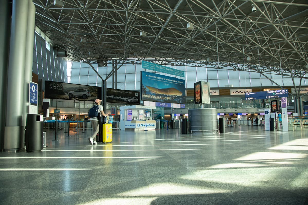 Helsinki-Vantaa lentoaseman terminaali 2 lähtöaula. Koko aula on lähes tyhjä. Yksi henkilö työntää keltaista pyörällistä matkalaukkuaan kohti turvatarkastusta.