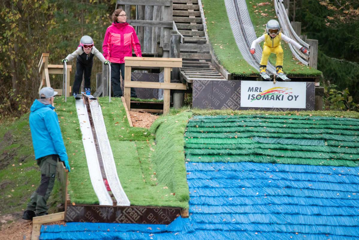 Anni Ahokas valmistautuu hyppyyn K2-mäessä, Martti Karhumaa hyppää K8-mäestä.