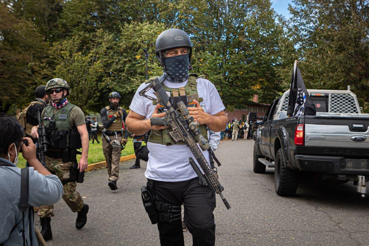 Aseistautuneita äärioikeistolaisen Proud Boys järjestön jäseniä. Kuvassa etualla olevalla miehellä on kypärä ja rynnäkkökiväärin kaltainen ase.