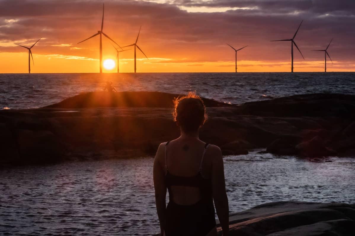 Nainen uimapuvussa katsoon auringonlaskua.