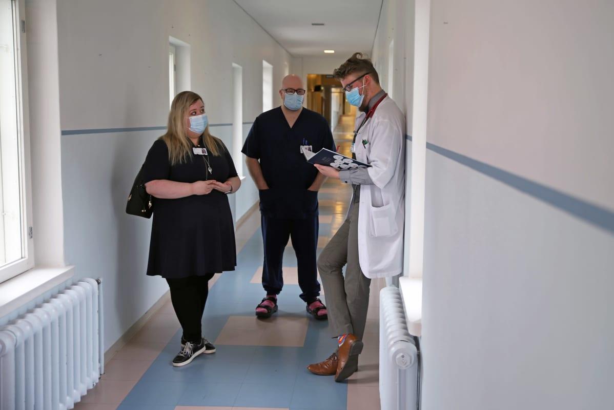 Lääkäri ja hoitajat keskustelemassa.