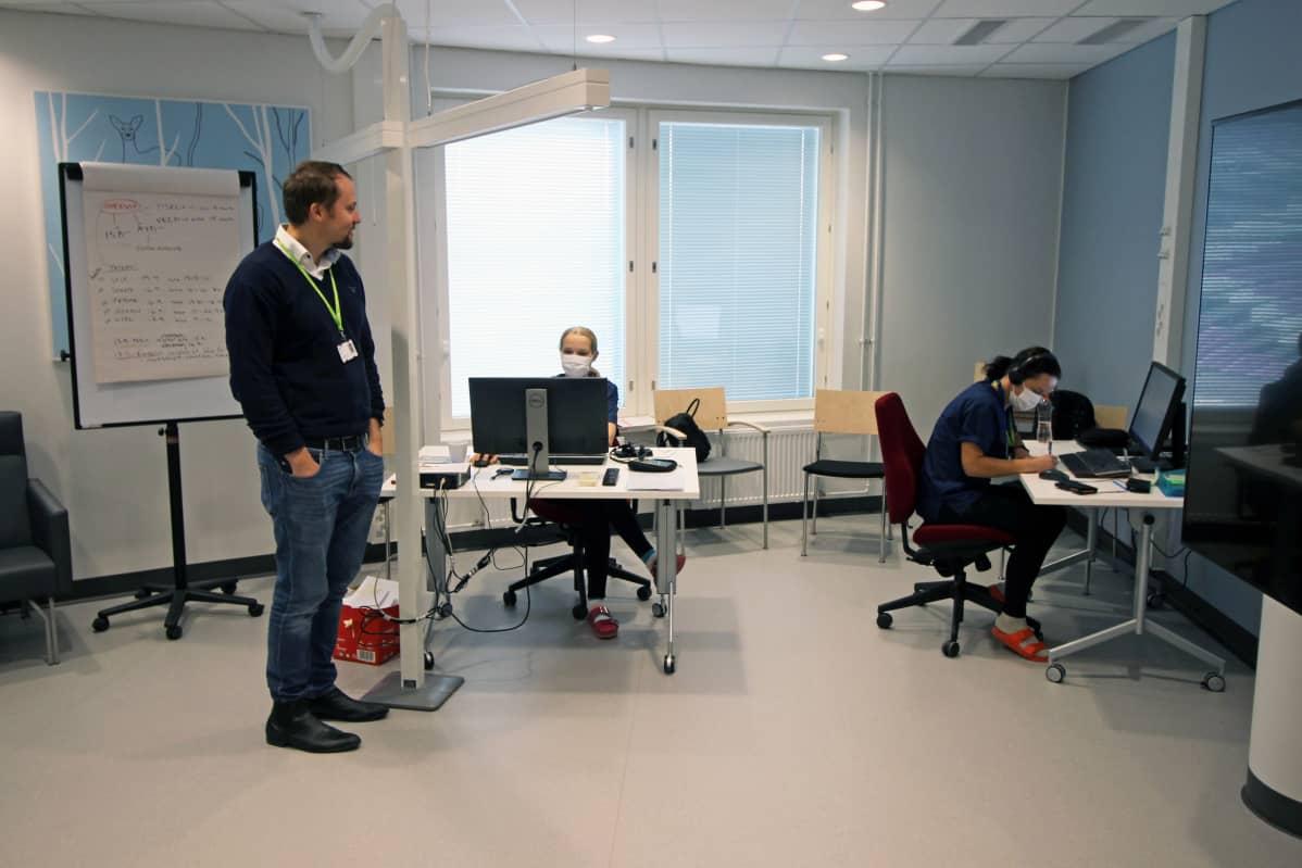 Santeri Seppälä ja kaksi sairaanhoitajaa Essoten tilassa, jossa jäljitetään koronatartunnan saaneiden liikkeitä.
