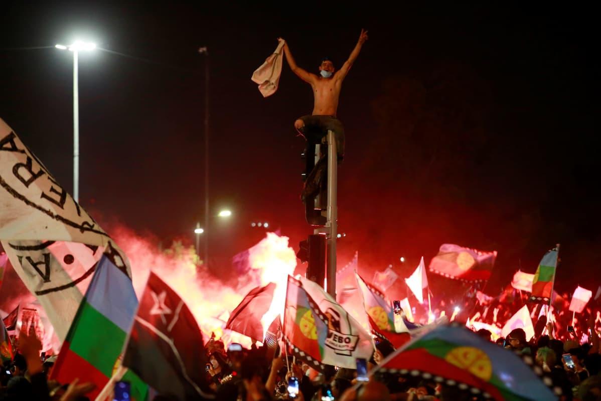 Mies juhli ilman paitaa  tolpan nokassa Santiago de Chilessä.