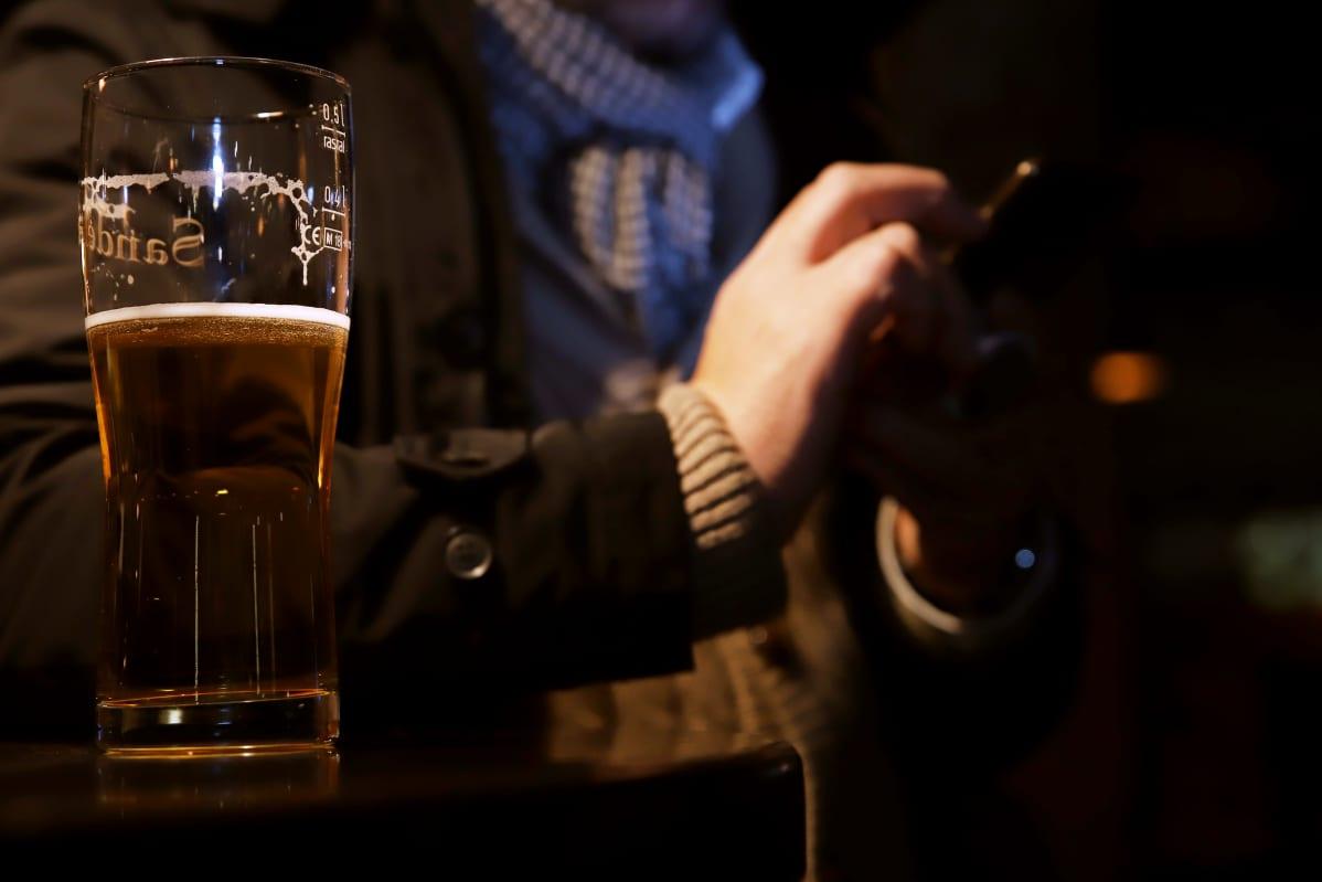 Mies oluen kanssa olutravintolan pöydässä