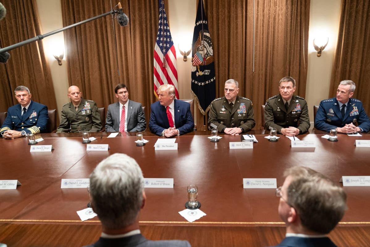 Trump istuu suuren pöydän ääressä, ympärillään amerikkalaisia kenraaleja eri aselajeista erilaisissa univormuissa.