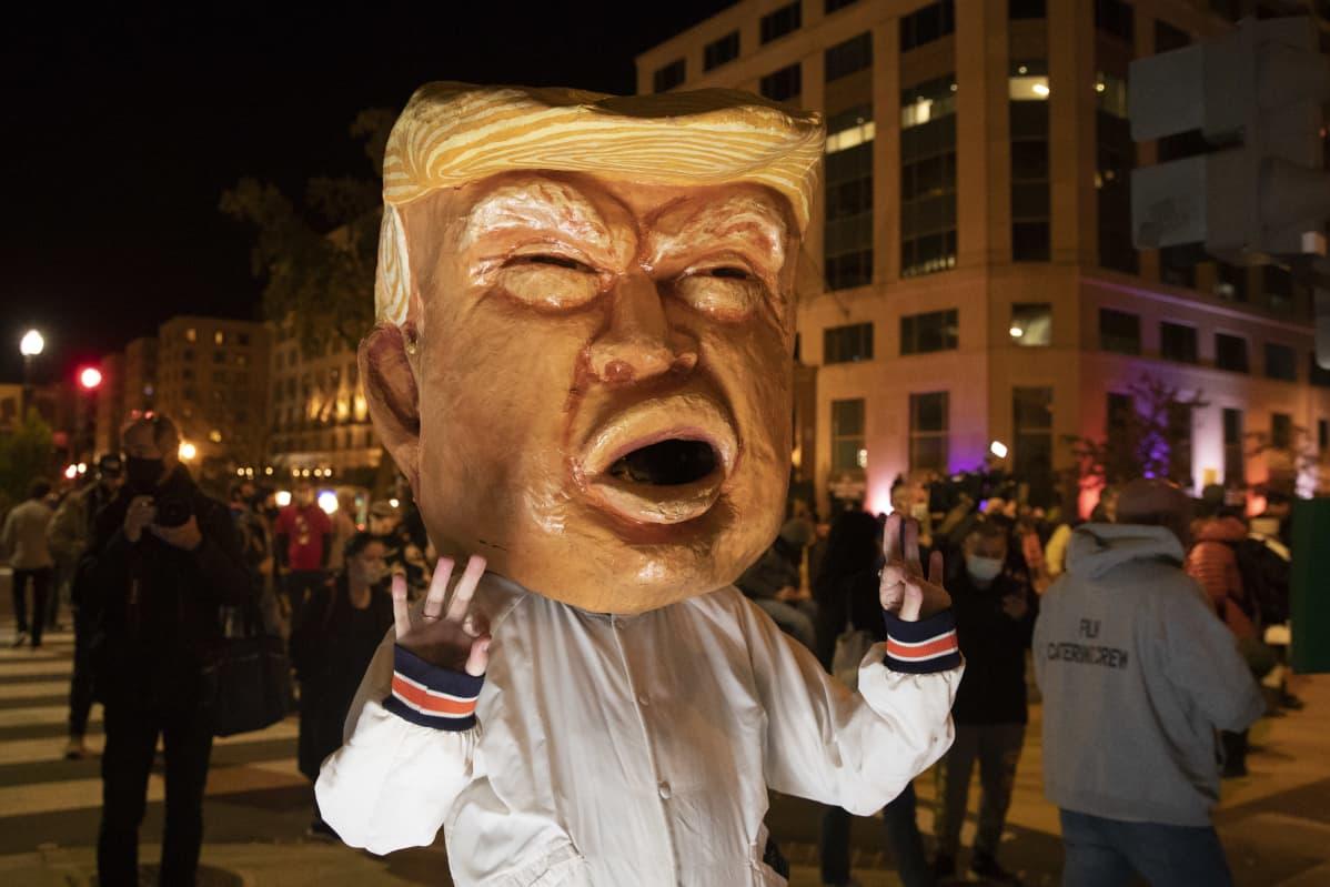 Mielenosoittaja kantoi Washingtonin keskustassa tiistai-iltana Trumpia esittävää päätä.