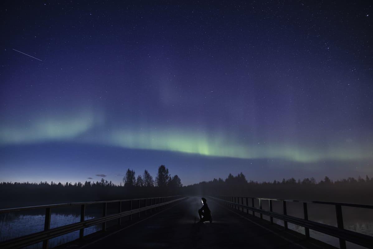 Revontulia taivaalla, mies polvillaan sillalla valoa kasvoilla.