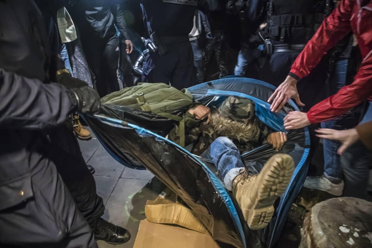 Poliisit ja mielenosoittajat kiskovat telttaa, josta näkyy jalka.