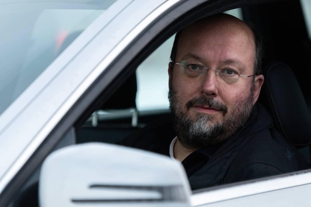 Jukka Aittokoski istuu taksin ratissa.