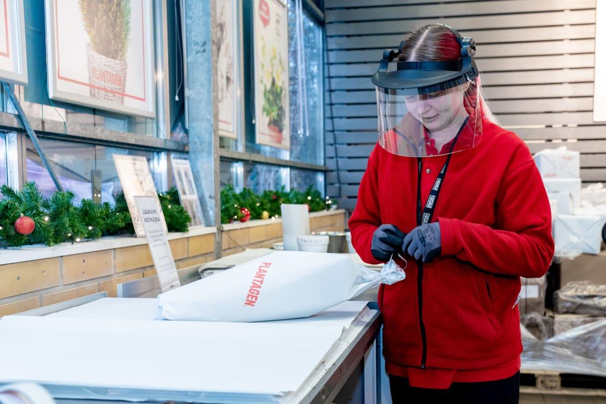 Heidi Mustonen pakkaa kukkakimppua Plantagenin myymälässä.