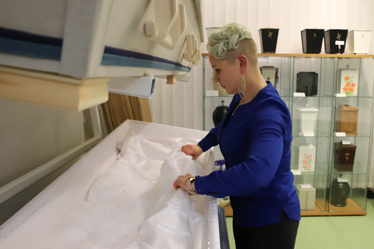 Minttu Väisänen asettelee peitteitä arkkuun hautaustoimistossaan.