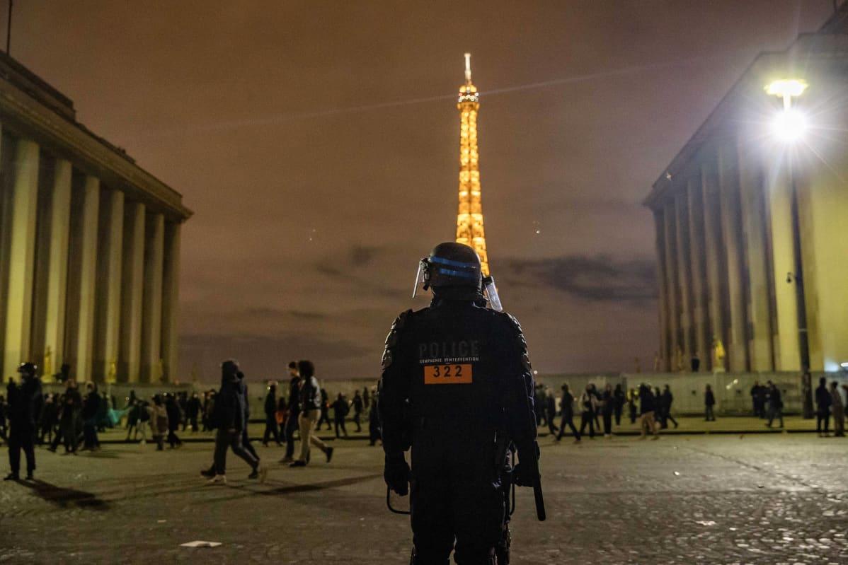 Poliisi seisoo selin kameraan. Taustalla Eiffel-torni.