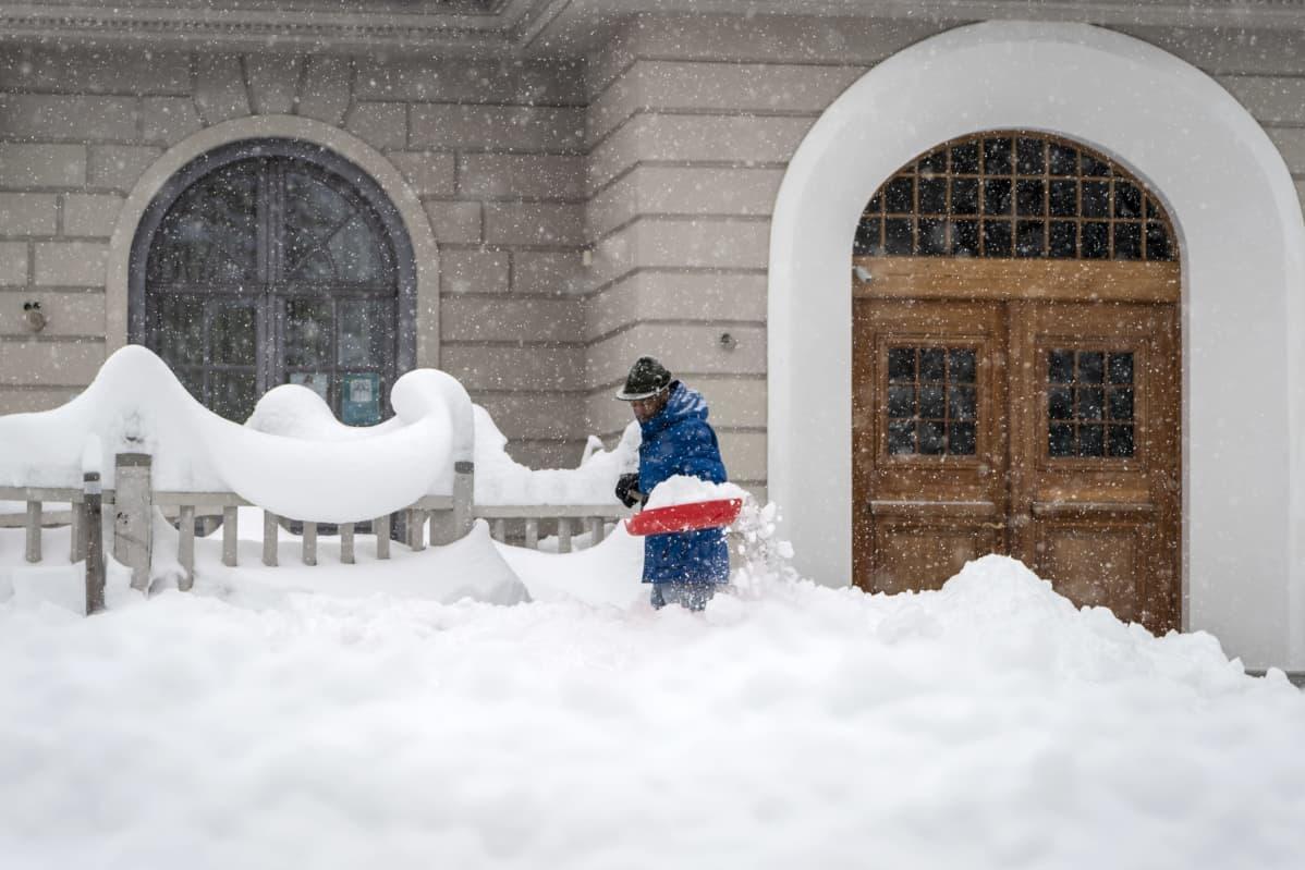 Syvässä lumessa lapioiva mies.