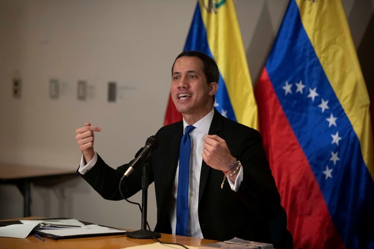 Juan Guaido istuu pöydän takana kädet koholla