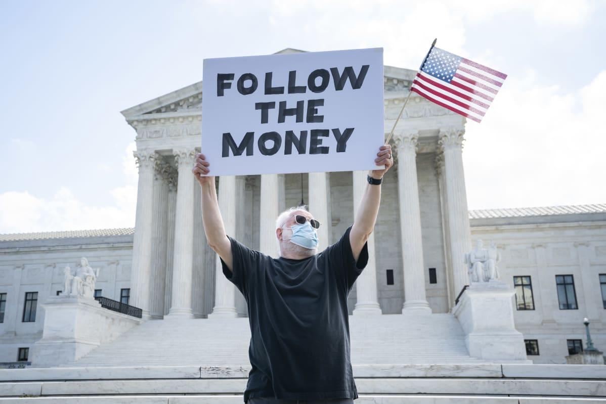 Follow the money -kylttiä kannatteleva mielenosoittaja Yhdysvaltain korkeimman oikeuden edessä heinäkuussa 2020. Trump yrittänyt saada korkeinta oikeutta estämään verotietojensa toimittamisen syyttäjälle..