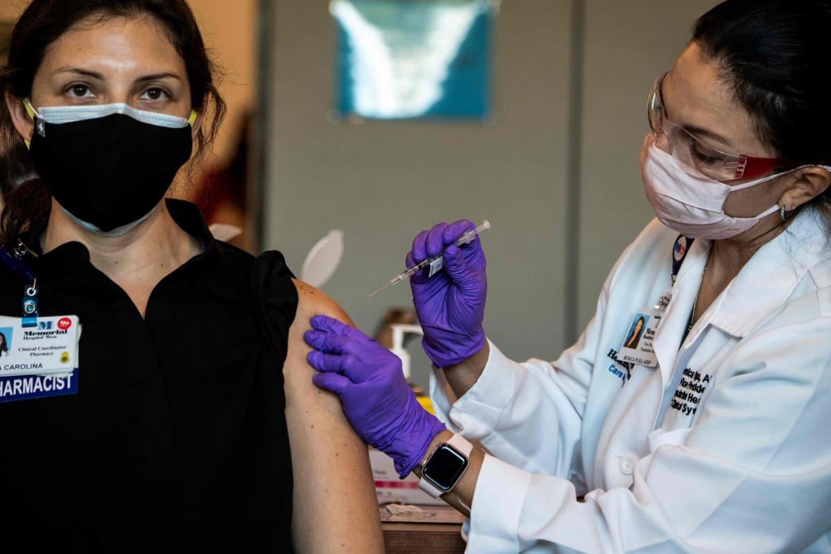 En kvinna som jobbar inom vården får en dos av Pfizer-Biontechs coronavaccin i Florida den 14 december 2020.
