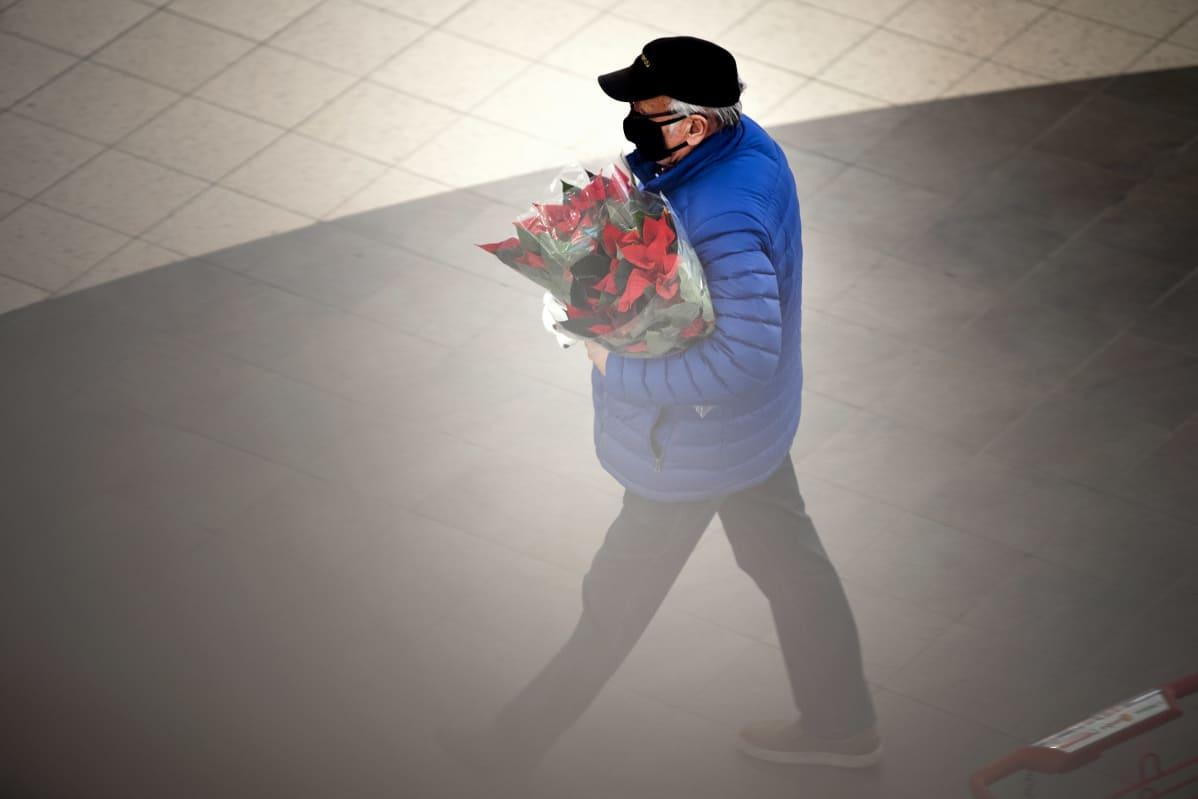 Mies kantaa joulukukkia ostoskeskuksessa.