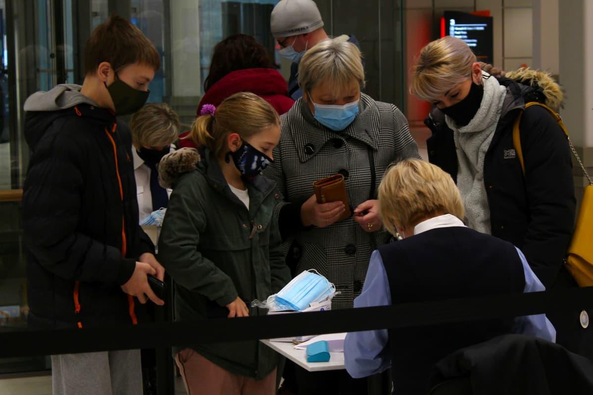 Ihmiset ojentavat henkilöllisyystodistukset päästäkseen etenemään Silja Europaan joka palvelee Tallinnassa kelluvana ostoskeskuksena.