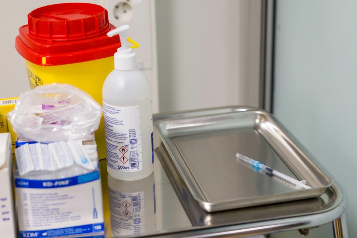 Koronarokotepiikki metalliastiassa. Vieressä on käsidesiä muita rokotuksessa tarvittavia välineitä.
