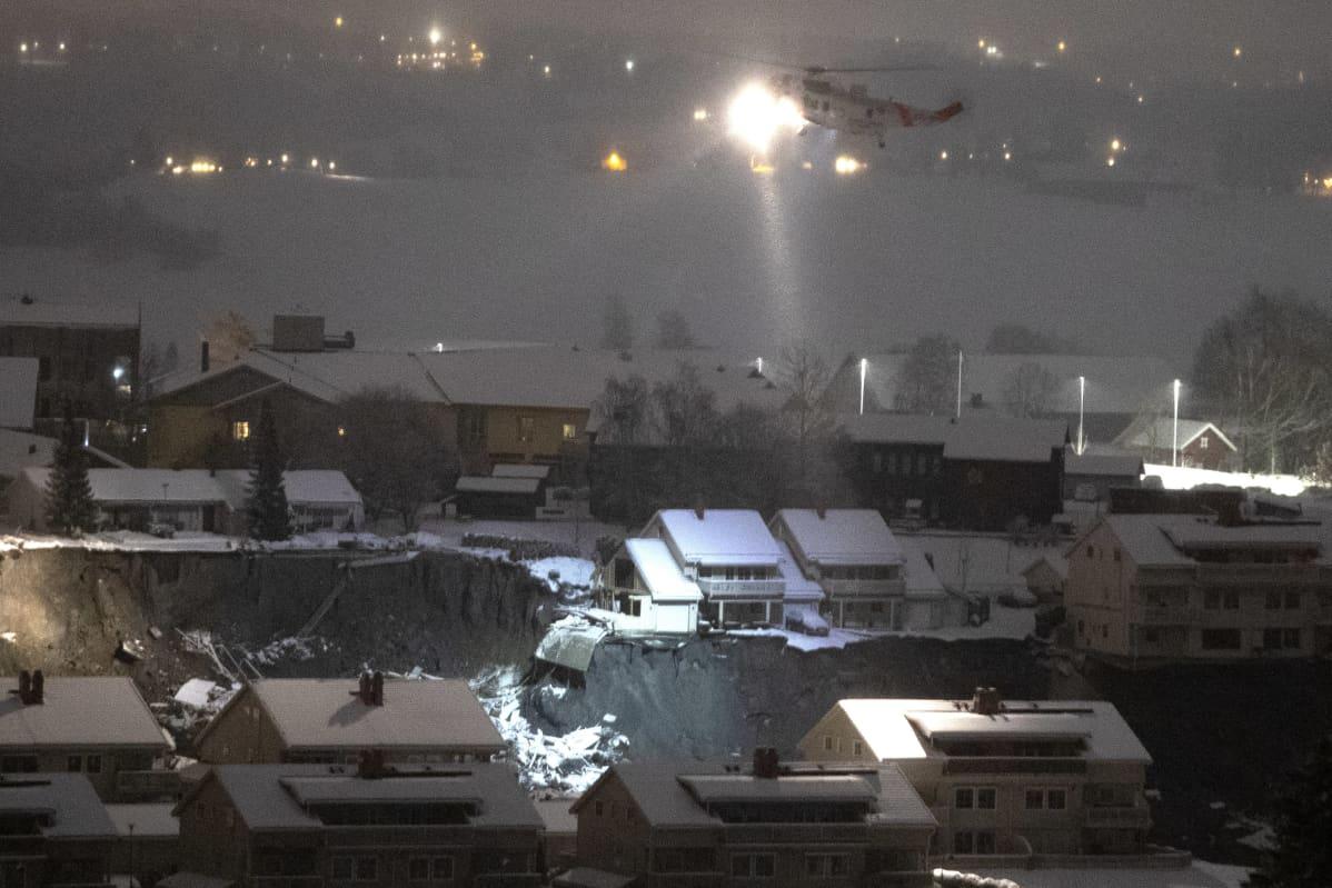 Helikopteri valaisee maanvyörypaikkaa.