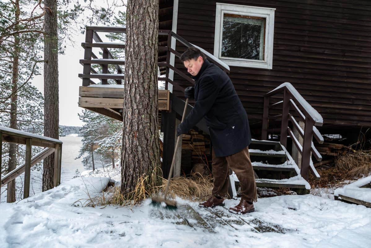 Maailman ilmatieteen järjestön pääsihteeri Petteri Taalas lakaisee lumia saunan edestä mökillään Nuuksiossa
