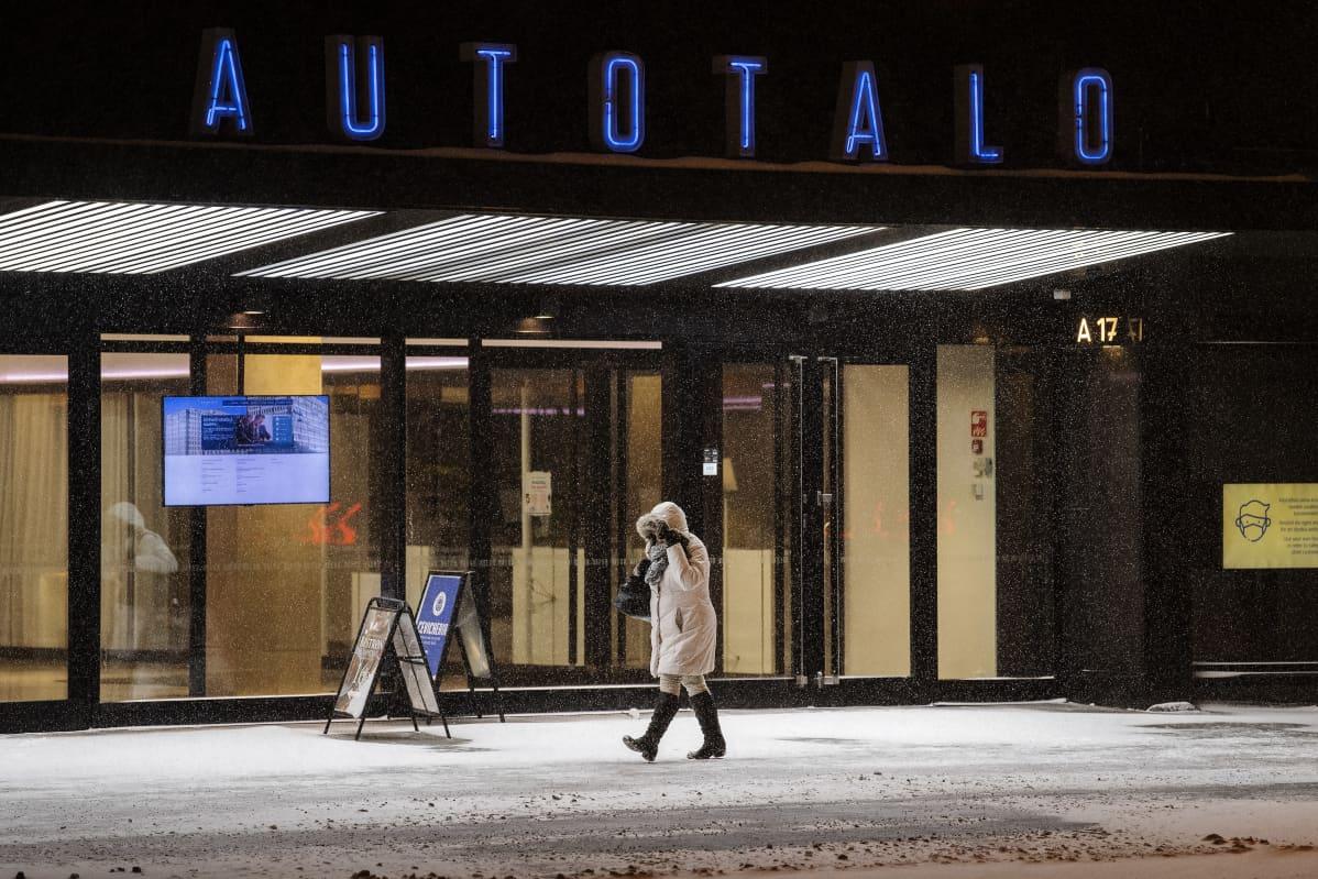 Henkilö suojaa itseään lumelta Autotalon edessä.
