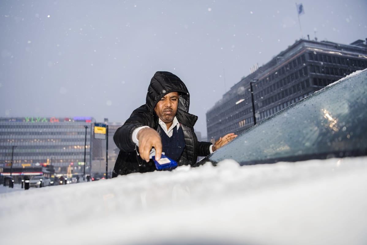Faisal Saleban skrapaa taksinsa tuulilasia.
