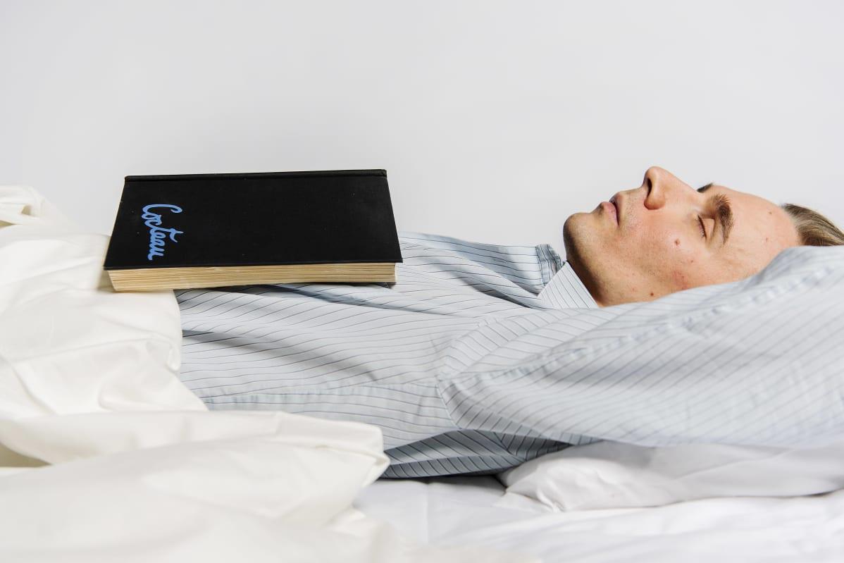 Niko Hallikainen makoilee sängyssä.