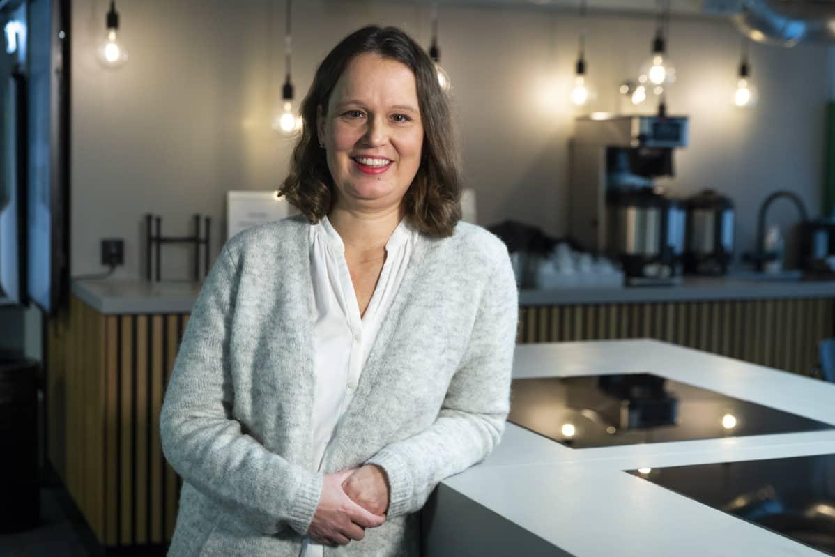 SOK:n kehityspäällikkö Mia Laakso nojaa pöydän kulmaan ja katsoo hymyillen kameraan.