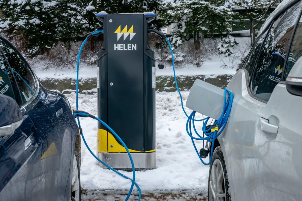 Kaksi sähköautoa latauksessa latauspisteellä talvella.
