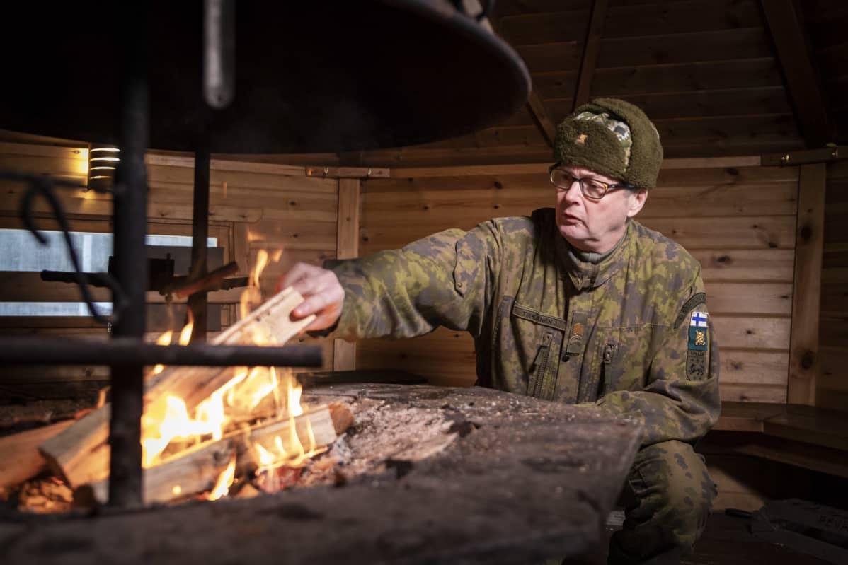 Jari Tikkanen lisää puita tuleen.