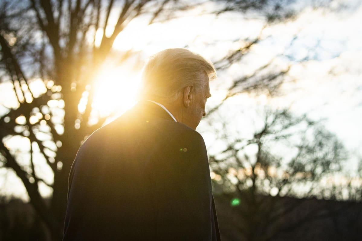 Donald Trump kuvattuna selkäpuolelta vastavaloon.