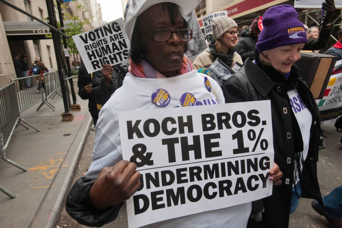 Musta nainen mielenosoituksessa, kyltissä vastustetaan mm. Kochin veljeksiä.