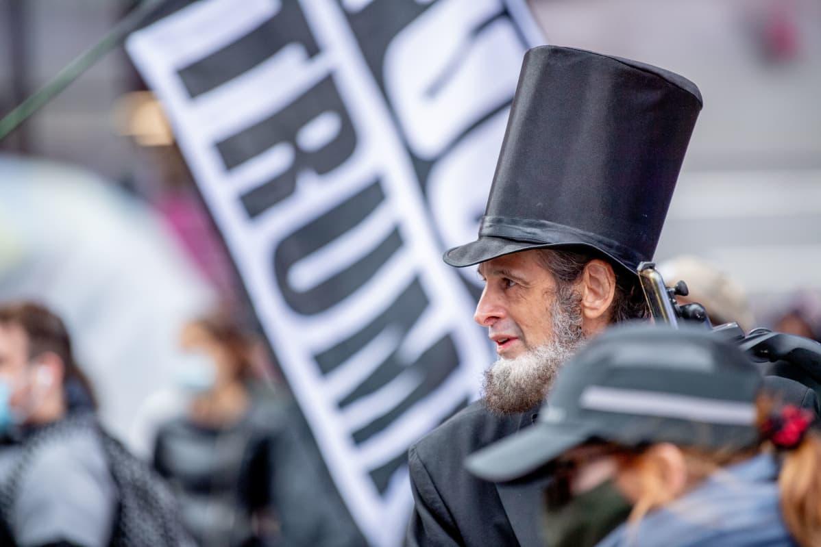 Abraham Lincolniksi pukeutunut mies ja Trump kyltti New Yorkissa.