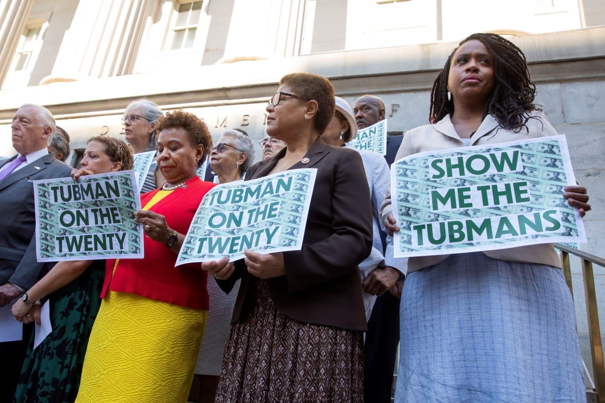 Ihmisiä Yhdysvaltain valtiovarainministeriön edustalla auringonpaisteessa. Etualalla on kolme demokraattiedustajaa, Barbara Lee, Karen Bass ja Ayanna Presley kylttien kanssa. Kylteissä vaaditaan Harriet Tubmanin kuvaa 20 dollarin seteleihin.