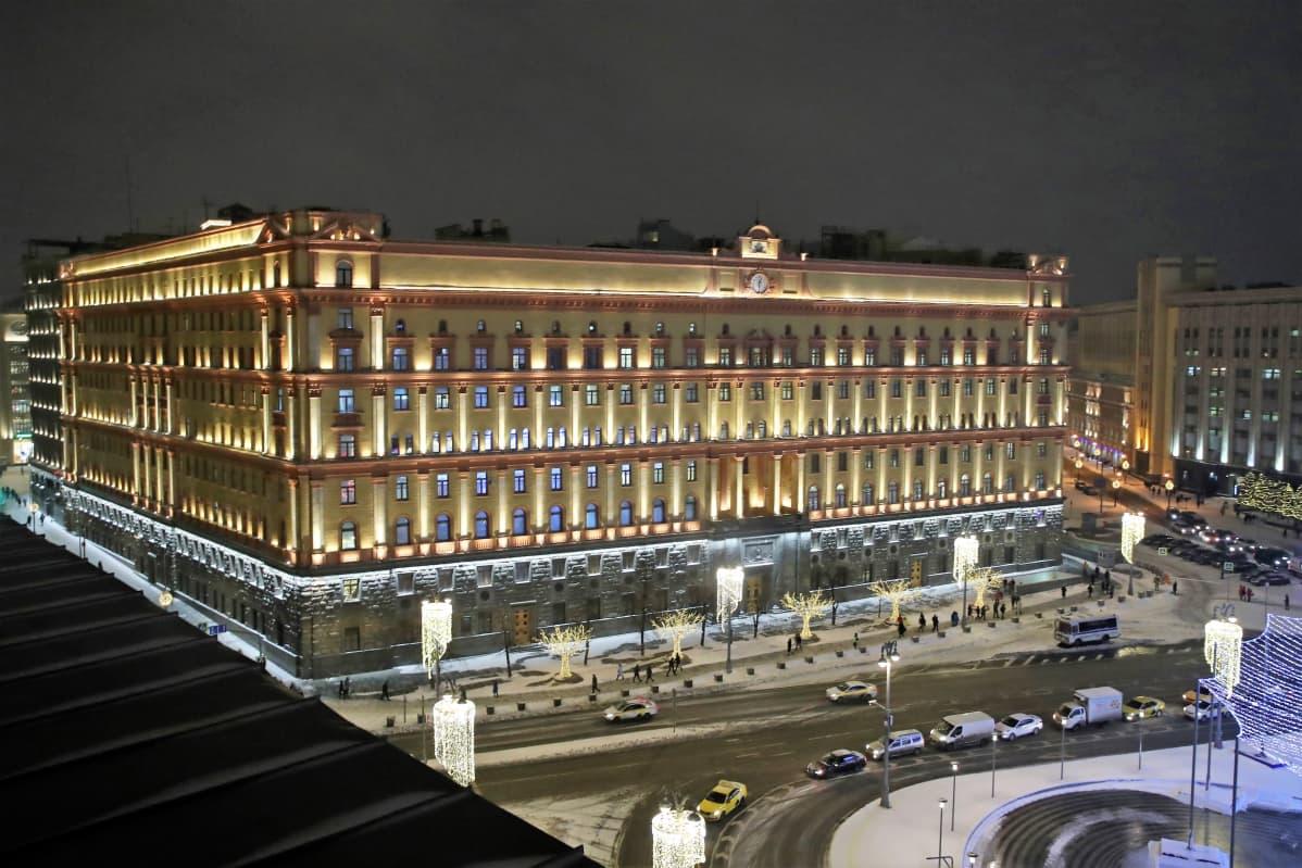 Venäjän turvallisuuspalvelun massiivisen uusbarokkisen päämajan julkisivut talvi-iltana. Rakennus on aukion laidalla. Kadulla sen edessä kulkee autoja. Maassa on lunta.