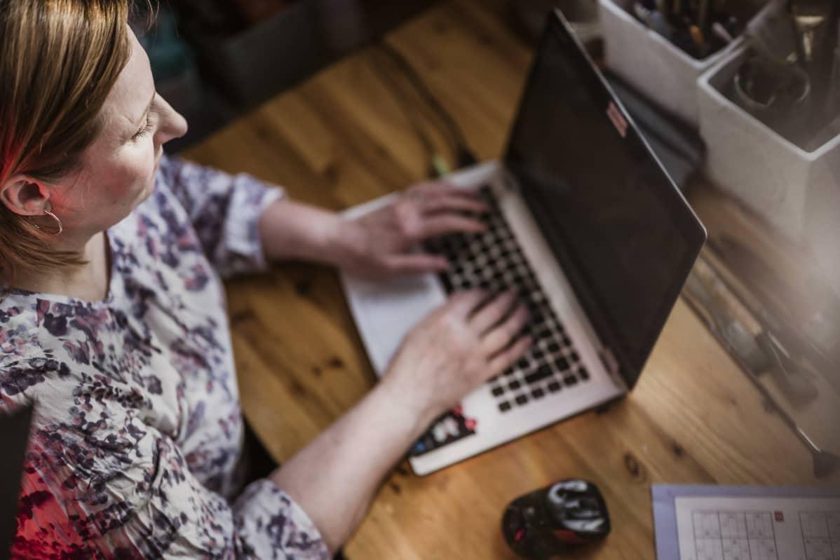Sinikka Svärd tietokoneensa ääressä.