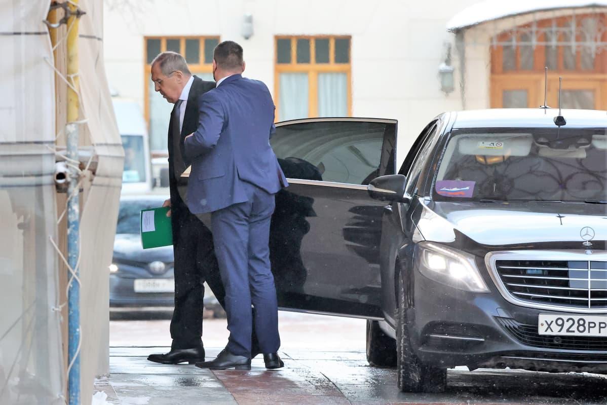 Lavrov on tulossa jalkakäytävän viereen pysähtyneestä mustasta autosta. Hänellä on tumma puku ja kravatti. Auton ovea pitelee auki mies sinisessä puvussa.