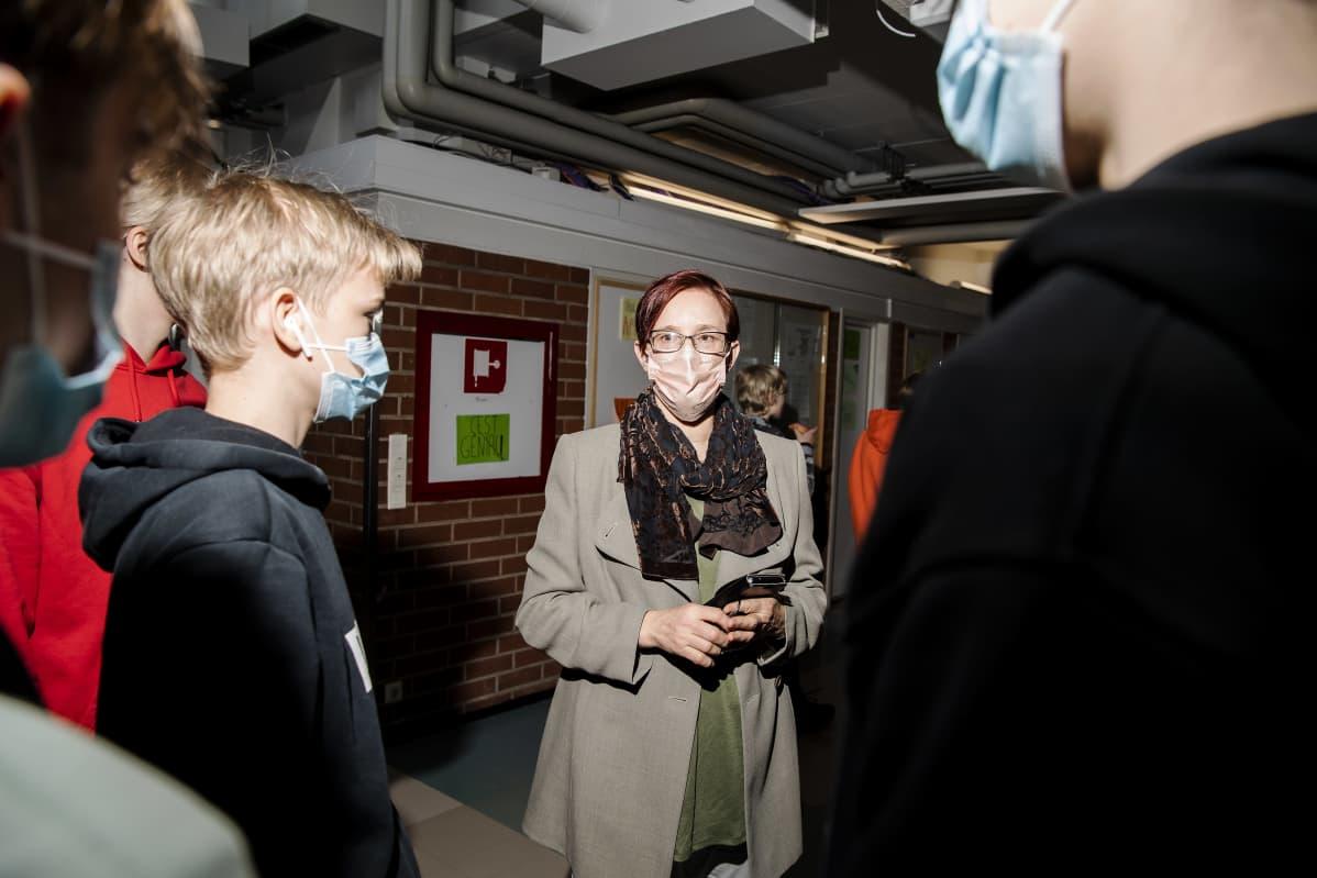 Outi Vilkuna pysähtyy juttelemaan oppilaille koulun käytävällä.