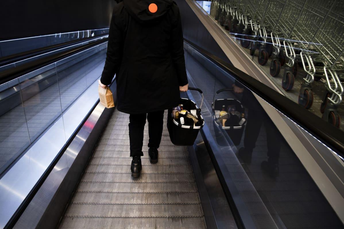 Asiakas kantaa noutoruokapussia ja ostoskoria kauppakeskuksen rullaportaissa.