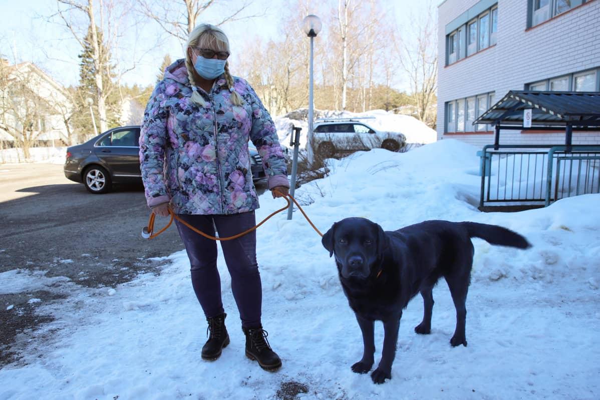 Erja Kulmala ja hänen koiransa Laku Kouvolan eläinsairaalan pihalla.