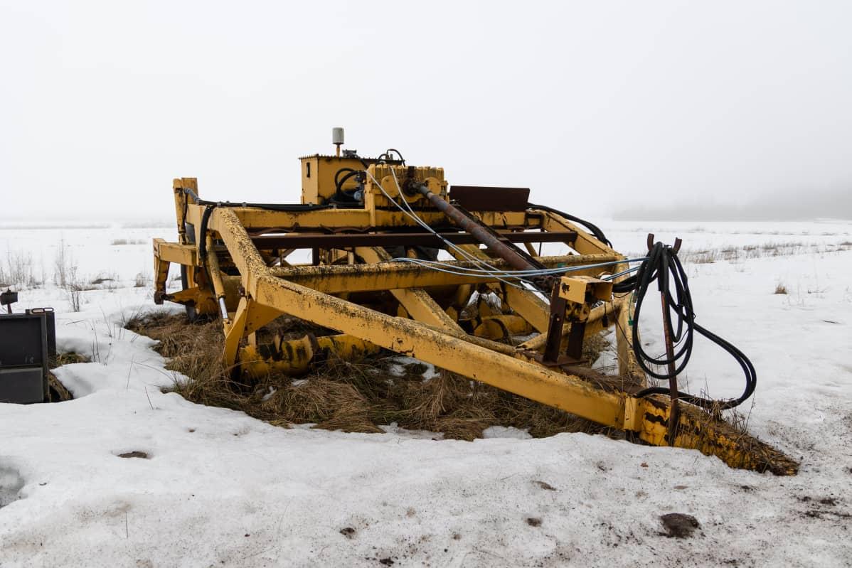Turvetuotantoon käytetty laite makaa lumessa Haukkasuolla Utin lähellä.