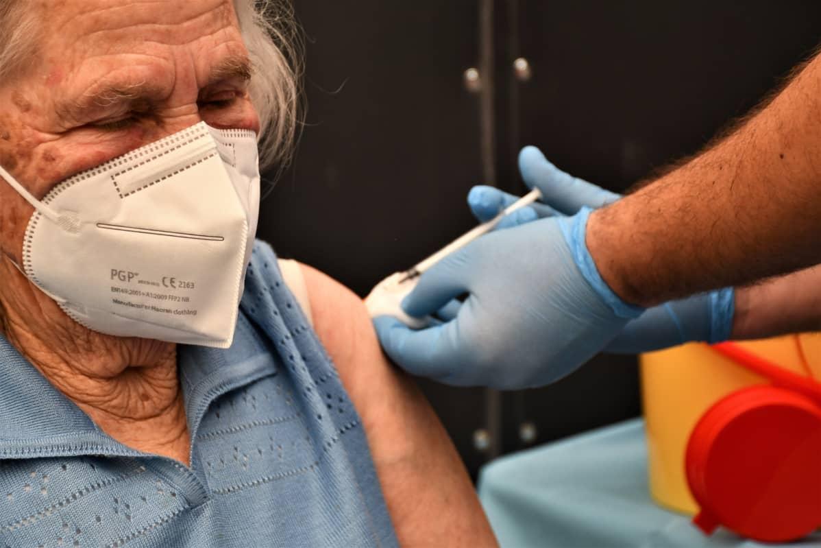Äldre italiensk kvinna får coronavaccinspruta.
